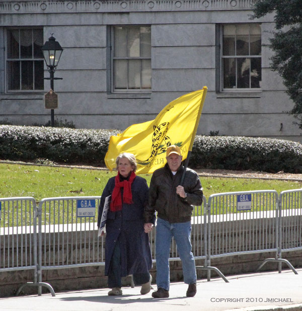 An older couple walk enroute to the Georgia State Capitol to participate in a Tea Party rally. They are holding hands and the man carries the Decatur Flag.