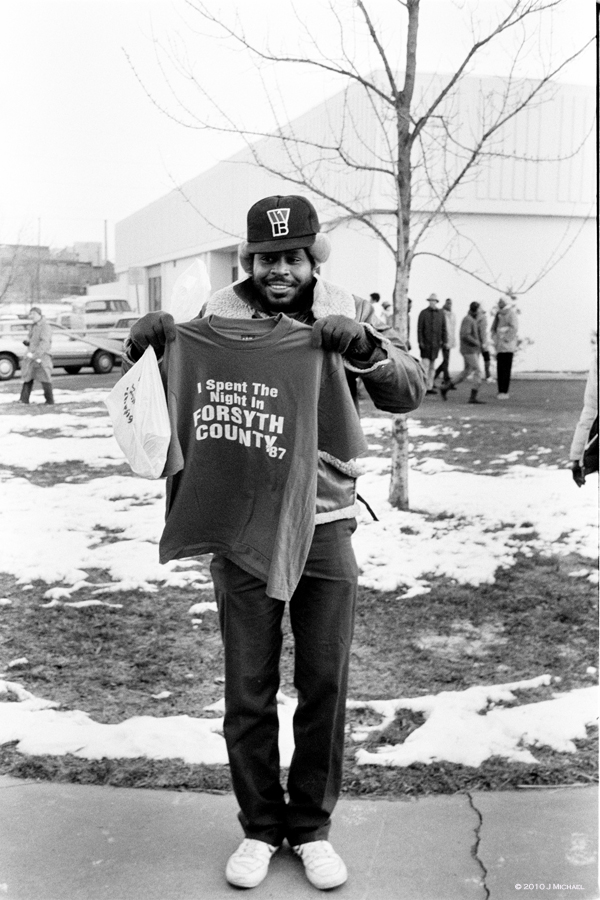 Man holds shirt with caption I Spent the Night in Forsyth County 1987