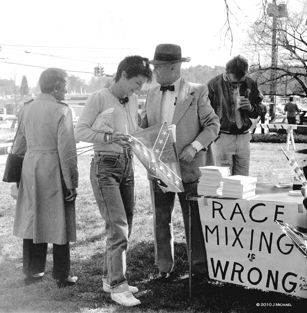 A woman looks at a book on a table with sign that say Race Mixing Is Wrong
