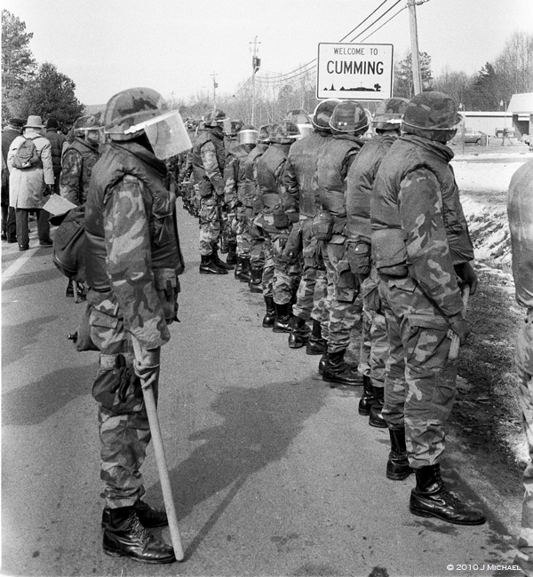 Georgia National Guard troops in front of sign that says Welcome to Cumming