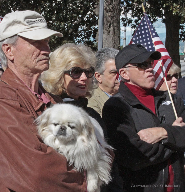 A couple attends the Tea Party rally with their dog. The lady is wearing sunglasses.